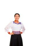 美丽的少妇站立的佩带的传统安地斯山的女衬衫和红色项链,举行在臀部武装,当微笑时 免版税库存照片