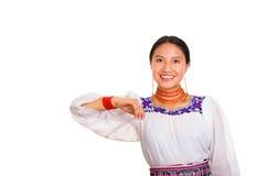 美丽的少妇站立的佩带的传统安地斯山的女衬衫和红色项链,互动的提供武装微笑 免版税库存照片