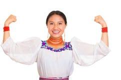 美丽的少妇站立的佩带的传统安地斯山的女衬衫和红色项链,互动的提供武装微笑 免版税图库摄影