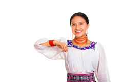 美丽的少妇站立的佩带的传统安地斯山的女衬衫和红色项链,互动的提供武装微笑 库存照片