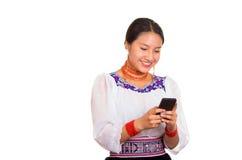 美丽的少妇站立的佩带的传统安地斯山的女衬衫和红色项链,拿着发短信的手机,当时 免版税库存图片