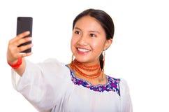 美丽的少妇站立的佩带的传统安地斯山的女衬衫和红色项链,拿着采取selfie的手机 库存图片