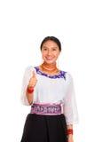 美丽的少妇站立的佩带的传统安地斯山的女衬衫和红色项链,给赞许,当愉快地时微笑 库存图片