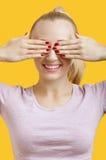 美丽的少妇覆盖物注视在黄色背景 免版税库存照片