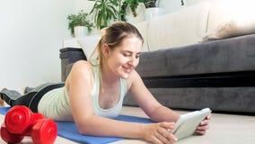 美丽的少妇说谎在地板上的在客厅和在片剂个人计算机的观看的体育运动 免版税库存图片