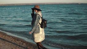 美丽的少妇走沿海,微笑和享受温暖的秋天天 女孩转过来并且微笑 股票录像