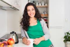 美丽的少妇食用茶在她的厨房 库存图片