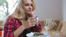 美丽的少妇饮用的咖啡和dreamingin在咖啡馆 股票视频