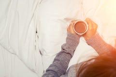 美丽的少妇饮用的咖啡在家在她的床wearin 免版税图库摄影