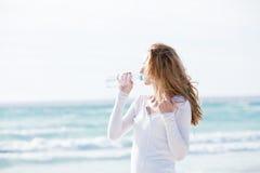 美丽的少妇饮用水在夏天 免版税库存照片