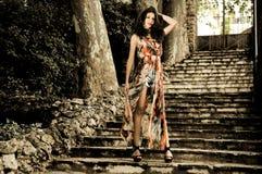 美丽的少妇,方式设计,在庭院台阶 免版税库存图片