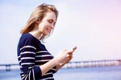 美丽的少妇,金发碧眼的女人,做提示户外使用智能手机和快速的4G互联网连接,当站立反对r时 免版税图库摄影