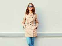 美丽的少妇戴典雅的外套黑色太阳镜站立在灰色 免版税库存照片