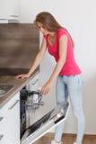 美丽的少妇组成在洗碗机的盘 免版税库存照片