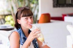 美丽的少妇画象咖啡馆饮用的鸡尾酒的 可口刷新的鸡尾酒在晴天 果汁饮料 免版税库存照片