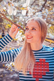 美丽的少妇画象在木兰开花的公园在一个晴天 有木兰花的微笑的女孩 愉快的女孩 免版税库存图片