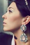 美丽的少妇画象有冠状头饰和耳环的。 免版税库存图片