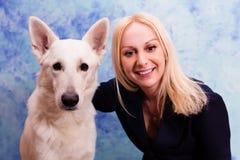美丽的少妇画象有狗的在蓝色背景 免版税图库摄影