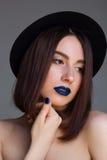 美丽的少妇画象有蓝色嘴唇的和帽子的 义卖市场 免版税库存图片