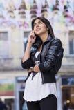 美丽的少妇画象谈话在室外的电话 库存图片