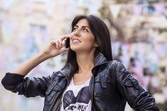 美丽的少妇画象谈话在室外的电话 免版税库存图片