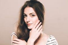 美丽的少妇画象逗人喜爱嫩纯净微笑接触她的下巴由手指有吸引力的自然背景 免版税库存图片