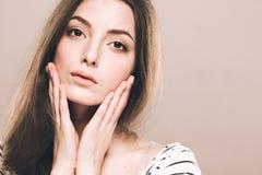 美丽的少妇画象逗人喜爱嫩纯净微笑接触她的面颊由手指有吸引力的自然背景 图库摄影