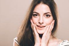 美丽的少妇画象逗人喜爱嫩纯净微笑接触她的面颊由手指有吸引力的自然背景 库存图片