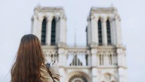 美丽的少年在减速火箭的影片照相机的女性为照相的Notre Dame在巴黎,法国,著名大教堂 股票录像