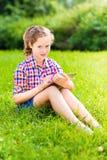 美丽的少年女孩坐与数字式片剂的草 图库摄影