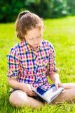 美丽的少年女孩坐草和阅读书 图库摄影