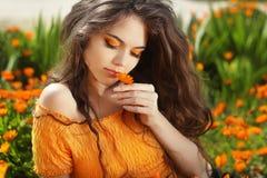美丽的少年式样女孩嗅到的花,在万寿菊流程 免版税库存照片