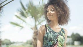 美丽的少年美国黑人的女孩画象摆在照相机的热带海滩的 免版税库存照片