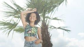 美丽的少年美国黑人的女孩画象摆在照相机的热带海滩的 免版税图库摄影
