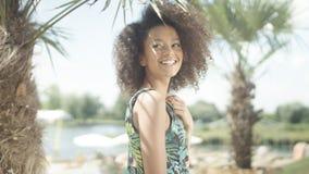 美丽的少年美国黑人的女孩画象摆在照相机的热带海滩的 库存照片