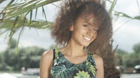 美丽的少年美国黑人的女孩画象摆在照相机的热带海滩的 免版税库存图片