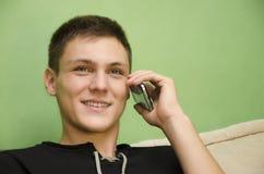 美丽的少年谈话在巧妙的电话 免版税库存照片