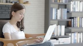 美丽的工作有微笑和愉快的开会的画象亚裔妇女网上膝上型计算机在长沙发在客厅 影视素材