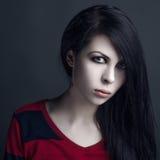 美丽的巫婆和万圣夜题材:一个女孩吸血鬼的画象有黑发的 免版税图库摄影