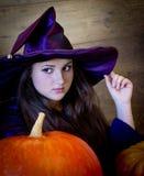 美丽的巫婆在与笤帚的紫色万圣夜 免版税库存图片