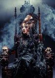 年轻美丽的巫婆坐椅子 明亮组成,头骨,烟万圣夜题材 免版税库存图片