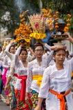 美丽的巴厘语妇女队伍传统服装的-布裙,在Ba的Galungan庆祝时运载提供在头 免版税库存图片