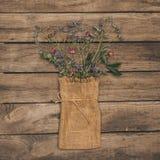 美丽的干花在土气木桌上的大袋袋子安排了 免版税图库摄影