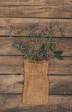 美丽的干花在木台式的大袋袋子安排了 免版税库存图片