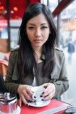 美丽的年轻亚裔在咖啡店的大阳台的妇女饮用的咖啡 库存照片