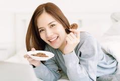 美丽的年轻亚裔在家吃曲奇饼的妇女佩带的毛线衣画象在床卧室,看照相机 放松和 免版税库存图片