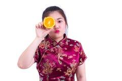 美丽的年轻亚裔妇女佩带的汉语穿戴传统cheongsam或qipao 接触她的面孔用水多的桔子的俏丽的女孩 免版税库存照片