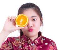 美丽的年轻亚裔妇女佩带的汉语穿戴传统cheongsam或qipao 接触她的面孔用水多的桔子的俏丽的女孩 库存照片