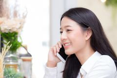 美丽的年轻亚裔妇女谈的电话和微笑在咖啡店,坐在咖啡馆业余时间的女实业家 库存图片