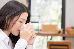 美丽的年轻亚裔妇女饮用的咖啡和微笑在咖啡馆、女孩坐在咖啡店的早餐和leisur的早晨 免版税库存图片